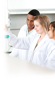 image of three medical laboratory technologists looking at flask contents